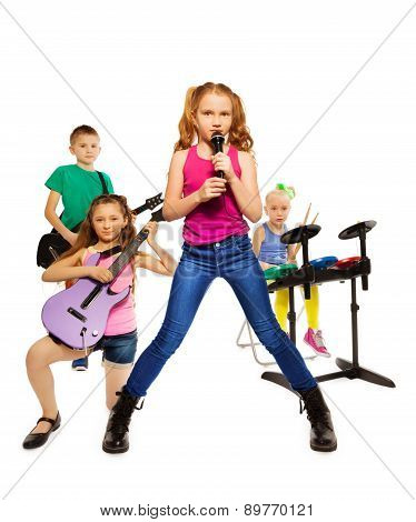 Children play musical instruments as rock group