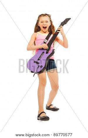 Excited girl with long hair playing on guitar