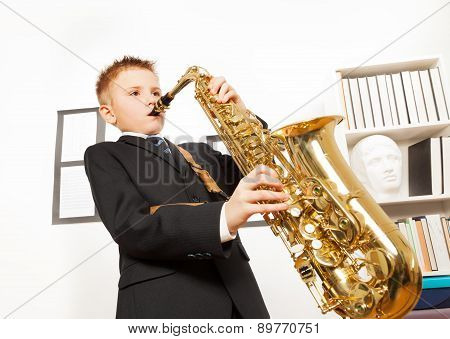 Boy in school uniform playing on alto saxophone