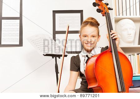 Smiling girl holds string to play violoncello