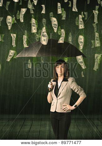 Businesswoman standing with umbrella in dollar bill rain concept on background