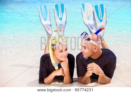 Happy diver couple lying down on the beach, wearing mask and flippers for snorkeling, enjoying extreme water sport, active summer time vacation