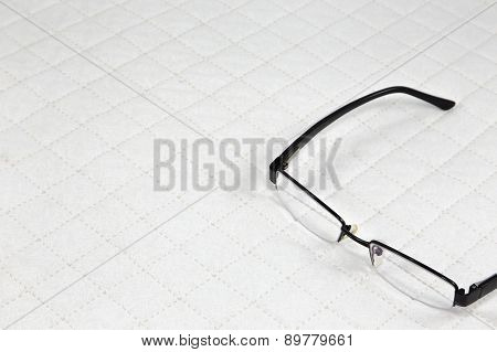 Eyeglasses Put On White Patchwork Quilt Background