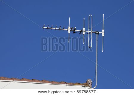 Rooftop television aerial against deep blue sky