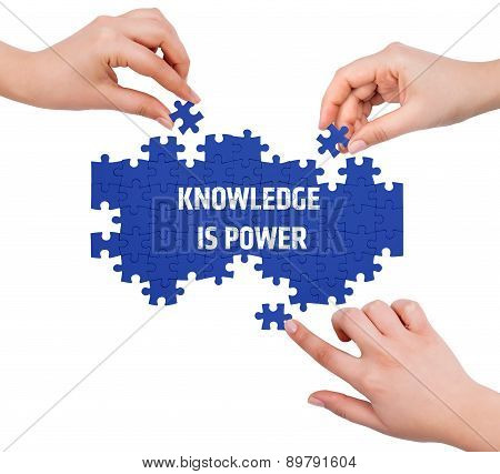 Hands With Puzzle Making Knowledge Is Power Word  Isolated On White
