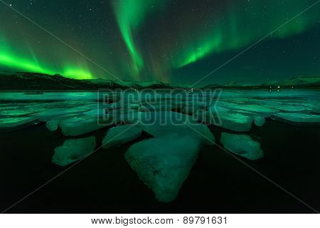 Northern Lights Aurora Borealis In The Night Sky Over Beautiful Lake Landscape.
