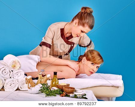 Young woman getting spa lastone therapy outdoor. Blue background.