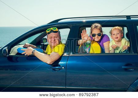 Father with two kids travel by car on sea vacation
