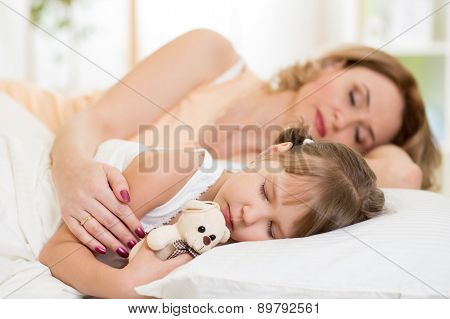 Child with mom preparing for napping on bed