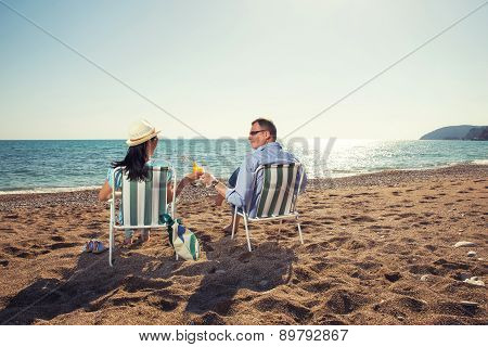 Middle aged couple sitting on deck chairs and enjoying the view of the sea