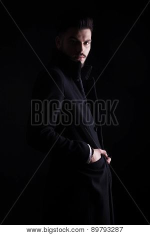 Side view picture of a handsome young business man looking at the camera while holding his hands in pockets.