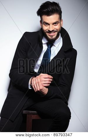 Happy young business man smiling to the camera while sitting on a stool.