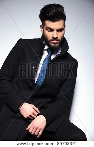 Attractive young business man looking down while sitting on a chair.