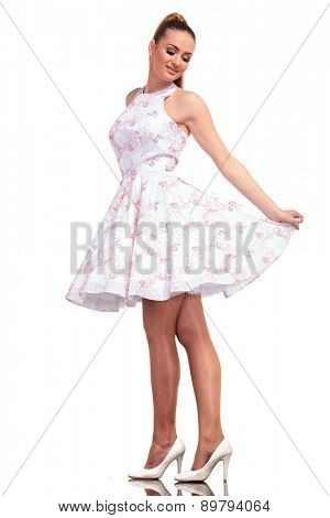 Smiling young fashion woman looking down while presenting her dress, on isolated background.
