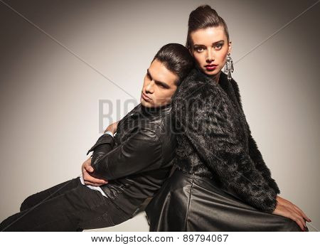 Tired young fashion man leaning on his lover while she is looking at the camera, both sitting on a white table.
