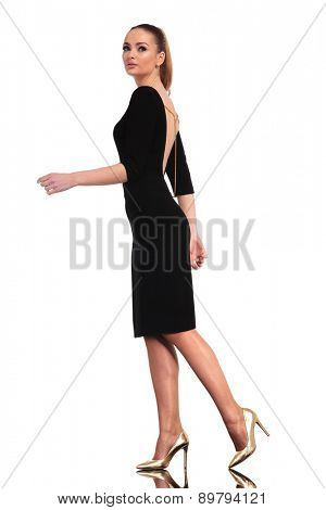 Full body picture of a elegant business woman walking on isolated studio background.