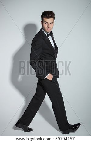 Side view picture of a elegant business man walking with his hand in pockets on grey studio background.