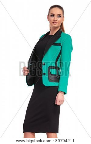 Side view of a elegant business woman pulling her jacket while looking away from the camera.
