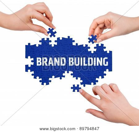 Hands With Puzzle Making Brand Building Word  Isolated On White