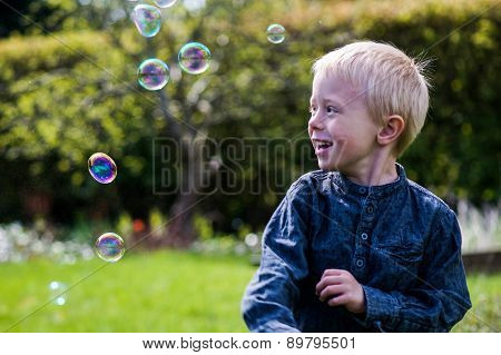 One Little Boy Blows Soap Bubbles In The Garden On A Summer Day