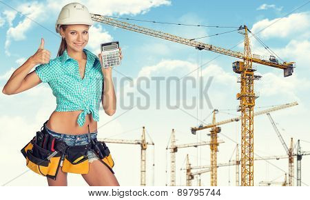 Young lady in hard hat holding calculator