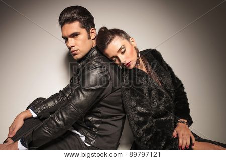 Young fashion woman sleeping on her lovers shoulder while he is looking at the camera.