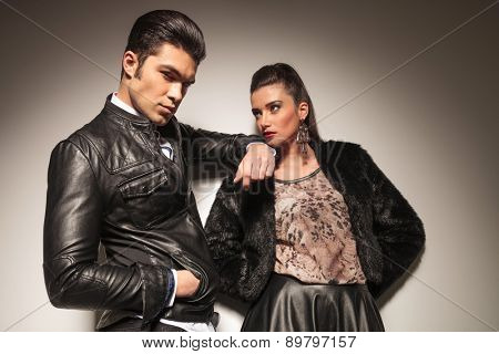 Handsome young fashion man holdnig his hand in pocket while leaning on his lover shoulder.
