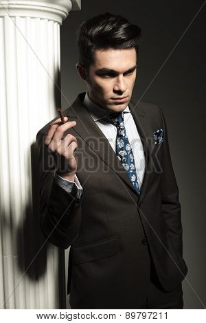 Portrait of a young business man looking down while holding a cigarette in his right hand.
