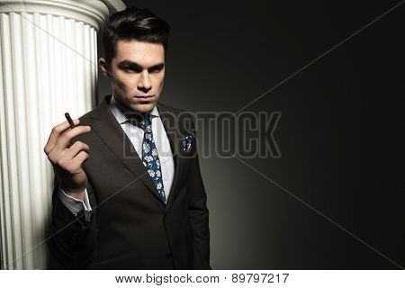 Handsome young business man holding a cigarette in his right hand while looking away from the camera.