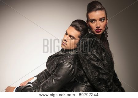 Close up picture of a handsome young fashion man leaning on his lover, both looking away from the camera.