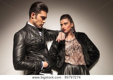 Beautiful young fashion woman leaning on a wall while her lover is lening on her.