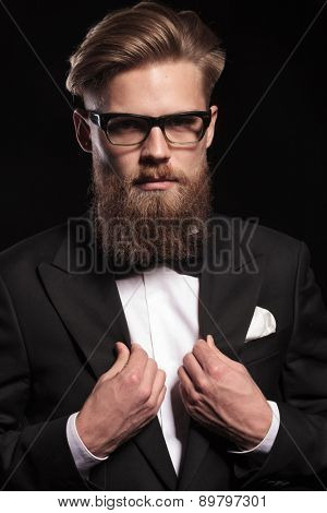 Close up picture of a blond business man fixing his collar, on black studio background.