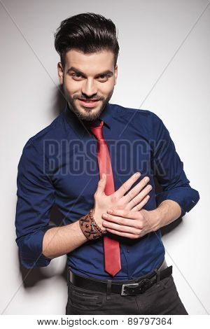Attractive young business man smiling at the camera while holding his hands together.