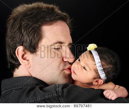 A Daddy holding and kissing his newborn daughter.  On a black background.