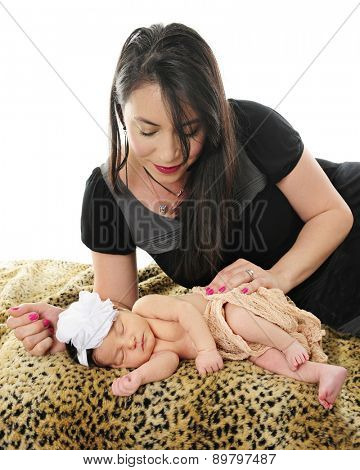 A loving mom adoring her newborn daughter who is sleeping contentedly on a leopard print blanket.  On a white background.