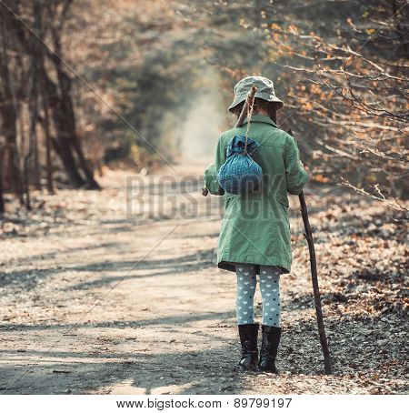 little girl goes on a footpath in the forest photo in retro style