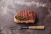 pic of slating  - Raw roast beef Rump and meat fork on dark stone slate background - JPG