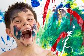 picture of mouth  - Funny artistic little boy with paint splodges on his face standing in front of his completed modern abstract creation laughing at the camera with his mouth wide open - JPG