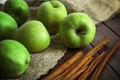 picture of sackcloth  - Green apples with cinnamon sticks on wooden table with sackcloth - JPG