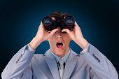 foto of binoculars  - Suprised businessman looking through binoculars against blue background with vignette - JPG