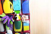 image of household  - Household chemicals in holder hanging on wooden door - JPG