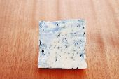 picture of french culture  - bit of aged french blue roquefort or cheese on wooden table - JPG