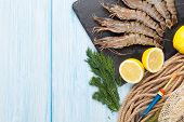 stock photo of tiger prawn  - Fresh raw tiger prawns and fishing equipment on wooden table - JPG