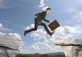 pic of gap  - Young businessman jumping over rocks with gap concept - JPG
