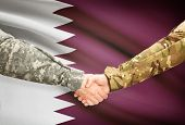 pic of qatar  - Soldiers shaking hands with flag on background  - JPG