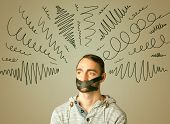 foto of taboo  - Young man with taped mouth and curly lines around his head   - JPG