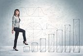 picture of climb up  - Business woman climbing up on hand drawn graphs concept on background - JPG