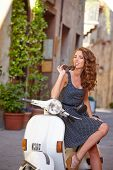 foto of scooter  - Young beautiful italian woman sitting on a italian scooter - JPG