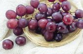 picture of sackcloth  - red grape in wooden basket over sackcloth - JPG