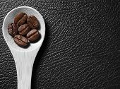 picture of coffee crop  - Coffee crop beans on bamboo spoon and leather texture background - JPG